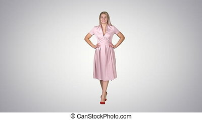 Woman in dress with hands on hips walking while looking at...