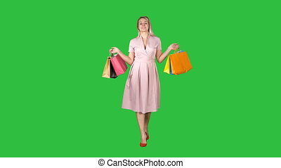 Young blonde girl in pink dress showing to camera shopping bags and walking on a Green Screen, Chroma Key.