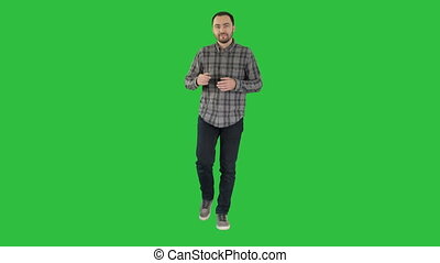 Young confident man in shirt and jeans walking towards camera and pointing to the sides on a Green Screen, Chroma Key.