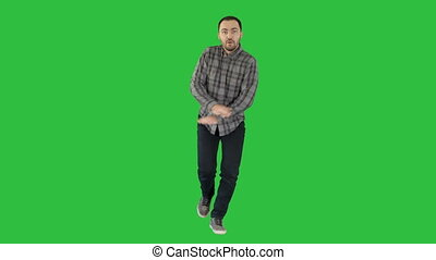 Young crazy man dancing and wanking forward on a Green Screen, Chroma Key.