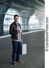 Full length portrait young happy smiling handsome traveller man in 20s leaving arrivals airport's lounge terminal building after collecting his baggage with a cup of fresh coffee
