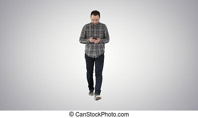 Young man walking and using a phone, messaging on gradient background.