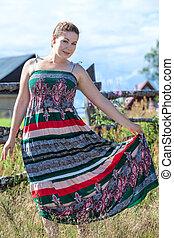Full-length pretty brunette posing in sundress in a field