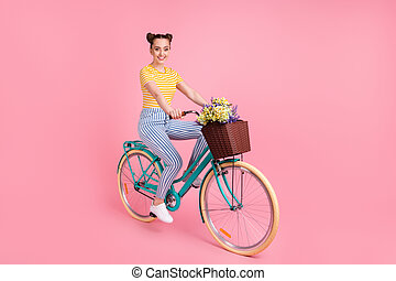 Full length profile photo of adorable girl sit on bicycle flowers in basket isolated on pink color background