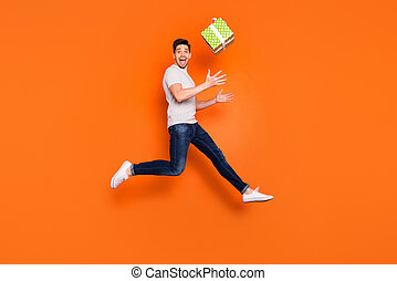 Full length profile photo of crazy guy jump high up catch big green giftbox unexpected present wear striped t-shirt jeans shoes isolated bright orange color background