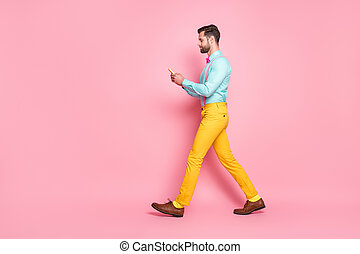Full length profile photo of handsome guy trend clothes browsing telephone writing new post walk street wear shirt suspenders bow tie yellow trousers isolated pastel pink color background