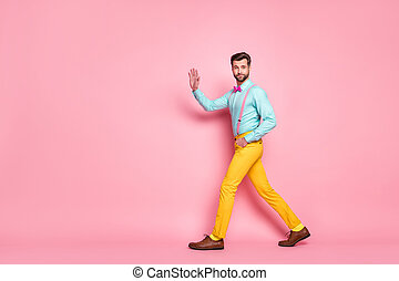 Full length profile photo of handsome guy trend look walk meeting red carpet celebrity waving hand wear shirt suspenders bow tie yellow pants footwear isolated pastel pink color background