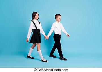 Full length profile photo of two girl boy classmates schoolchildren smiling hold hands morning walk to school wear uniform white shirt black pants dress isolated blue color background