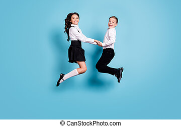 Full length profile photo of two opposite little girl boy schoolchildren brother sister classmates jump hold hands celebrate wear white shirt black pants dress isolated blue color background