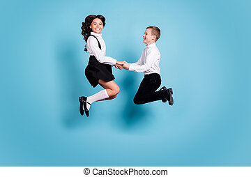 Full length profile photo of two opposite little girl boy schoolchildren classmates jump hold hands fun after school wear white shirt black pants dress isolated blue color background