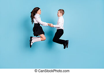 Full length profile photo of two opposite small girl boy schoolchildren brother sister classmates jump hold hands having fun wear white shirt black pants dress isolated blue color background
