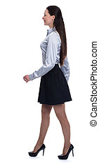 Full length profile portrait of a happy young woman walking