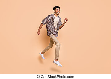 Full length profile portrait of carefree handsome dark skin guy look empty space isolated on beige color background