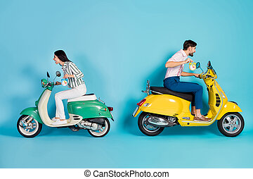 Full length profile side photo crazy two people biker hold clock ride fast road route dont want overtime yellow green motor bike party wear formalwear shirt pants isolated blue color background