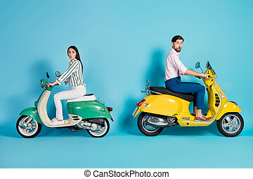 Full length profile side photo of shocked two people man woman ride motor bike impressed by high fast speed scream wow omg wear shirt white pants trousers isolated over blue color background