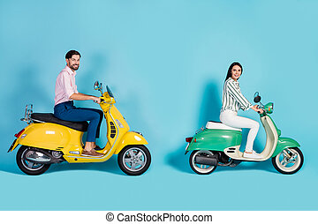 Full length profile side photo positive wife husband bikers drive yellow green motorcycle enjoy street trip wear white striped shirt pink pants trousers isolated blue color background