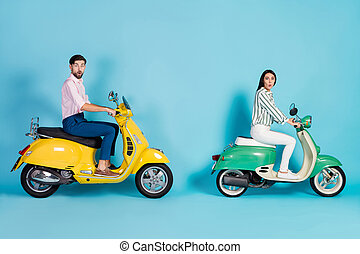 Full length profile side photo wife husband drive yellow green choppers impressed fast speed trip adventure scream wow omg wear striped shirt pants trousers isolated blue color background