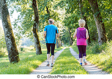 Full length rear view of a senior couple jogging together outdoo