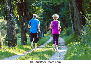 Full length rear view of a senior couple jogging together outdoors