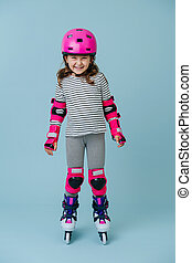 Full-length roller skating girl in protective gear on the ...