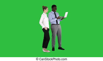 Satisfied of their work man and woman looking in the laptop on a Green Screen, Chroma Key.