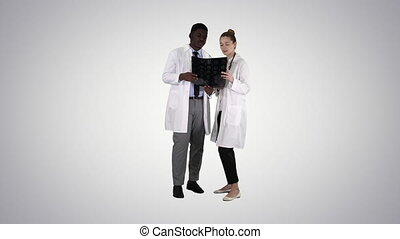 Serious nice woman doctor and afro american doctor study brain x ray on gradient background.