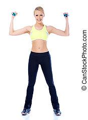 Full length shoot of sporty female with dumbbell