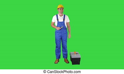 Full length shot. A repairman holding a toolbox and wrench smiling to camera on a Green Screen, Chroma Key. Professional shot in 4K resolution. 014. You can use it e.g. in your commercial video, business, presentation, broadcast