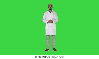 Arab doctor man in medical coat talking and presenting with hand something on a Green Screen, Chroma Key.