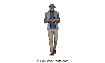 Arab presenter in casual walking with tablet and swiping pages on it on white background.