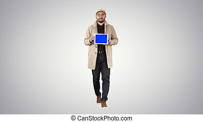 Attractive man holding tablet with blue key screen mockup on gra