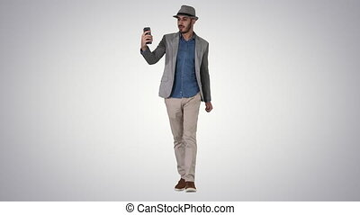 Attractive man in casual clothes hat hipster stylerecording vlog or making a video call on gradient background.