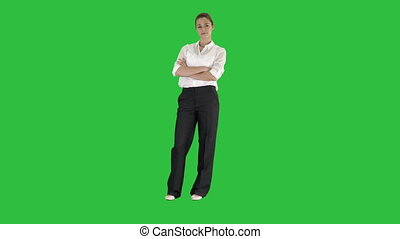 Attractive smiling businesswoman standing with arms folded and looking at camera on a Green Screen, Chroma Key.