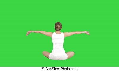 Beautiful young woman wearing sportswear practicing yoga sitting in lotus pose on a Green Screen, Chroma Key.