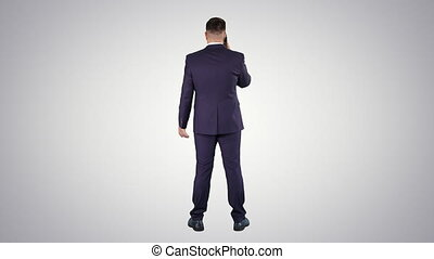 Businessman with smartphone, making a phone call on gradient background.