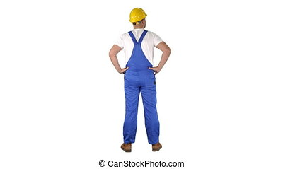 Engineer in construction helmet standing with hands on hips looking around on white background.