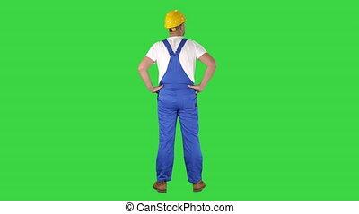 Engineer in construction helmet standing with hands on hips...
