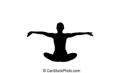 Silhouette Beautiful young woman wearing sportswear practicing yoga sitting in lotus pose.