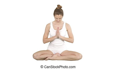 Beautiful young woman yogi rising her eyes to camera and smiles sitting in lotus pose on white background.