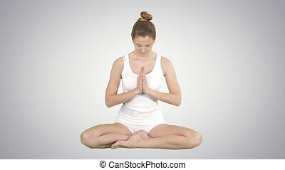 Beautiful young woman yogi rising her eyes to camera and smiles sitting in lotus pose on gradient background.