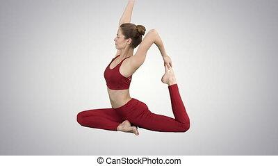 Beautiful young womandoing yoga or pilates exercise One Legged King Pigeon pose, Eka Pada Rajakapotasana on gradient background.