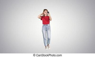 Blonde walking and preening looking in the phone on gradient...
