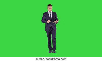 Businessman walking and swiping pages on his tablet computer...