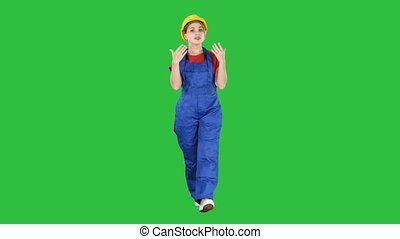Cheerful female construction worker talking to camera on a Green Screen, Chroma Key.