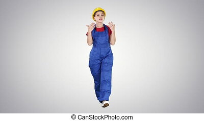 Cheerful female construction worker talking to camera on gradient background.