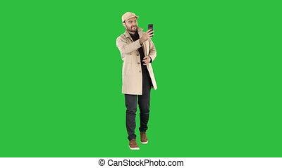 Cheerful man in coat taking photo making selfie on a Green Screen, Chroma Key.