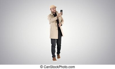 Cheerful man in coat taking photo making selfie on gradient background.