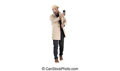 Cheerful man in coat taking photo making selfie on white background.