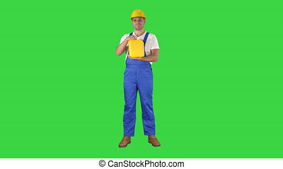Full length shot. Construction worker advertising construction material in canister on a Green Screen, Chroma Key. Professional shot in 4K resolution. 014. You can use it e.g. in your commercial video, business, presentation, broadcast