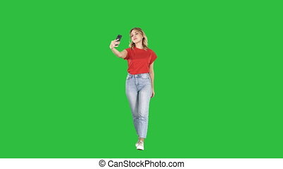 Cute sexy girl with blond curly hair walking and making selfie on a Green Screen, Chroma Key.
